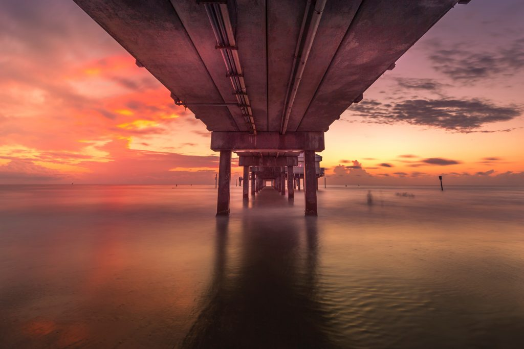 gray concrete bridge over the sea during sunset