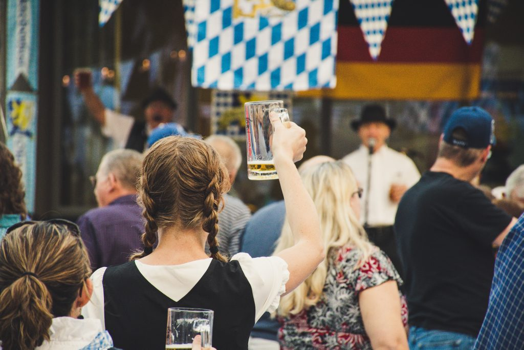 Woman standing in a crowd holding up beer glass